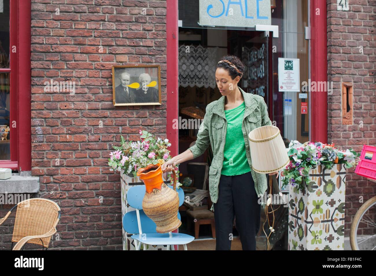 Female customer with jug and lamp outside vintage shop - Stock Image