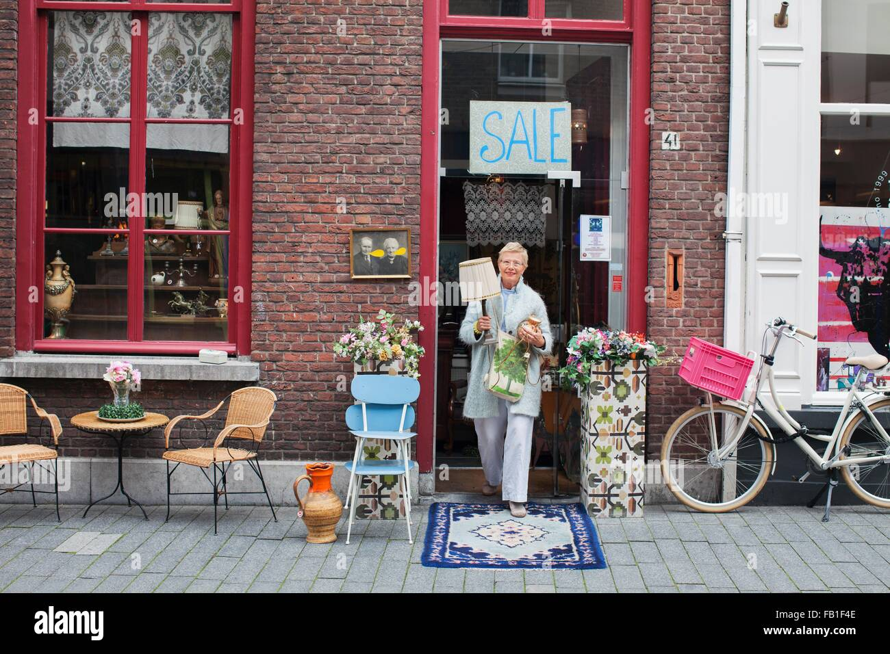 Mature female customer carrying lamp outside vintage shop - Stock Image