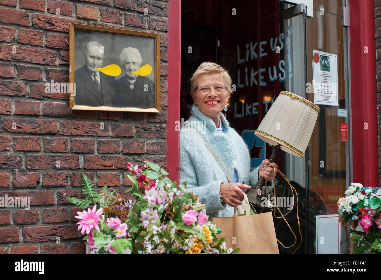 Mature female customer carrying lamp and shopping bag outside vintage shop - Stock Image