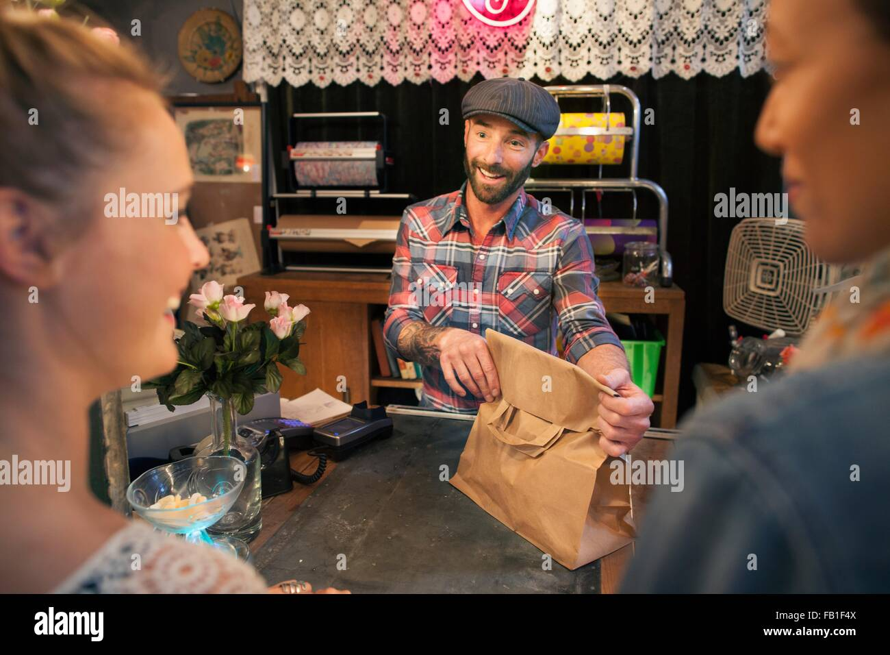 Two young female customers buying from vintage shop - Stock Image