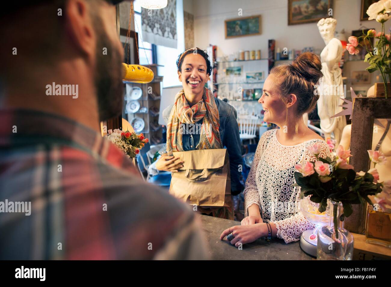 Two happy young female customers buying from vintage shop - Stock Image