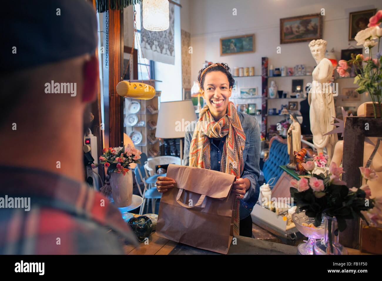 Happy young female customer buying from vintage shop - Stock Image