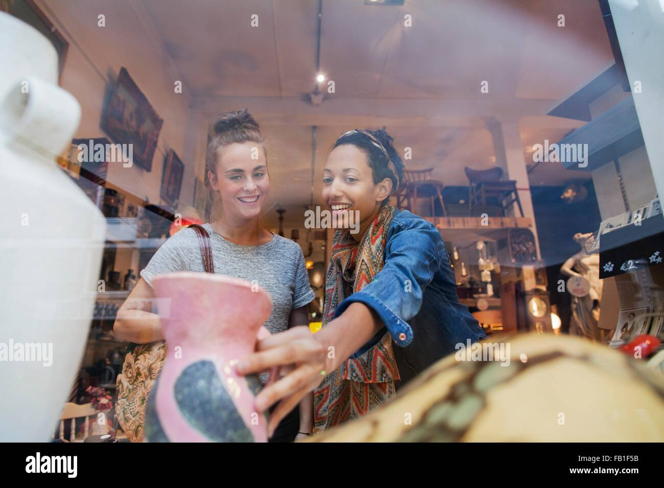 Young woman shopping for pink vase in vintage shop - Stock Image