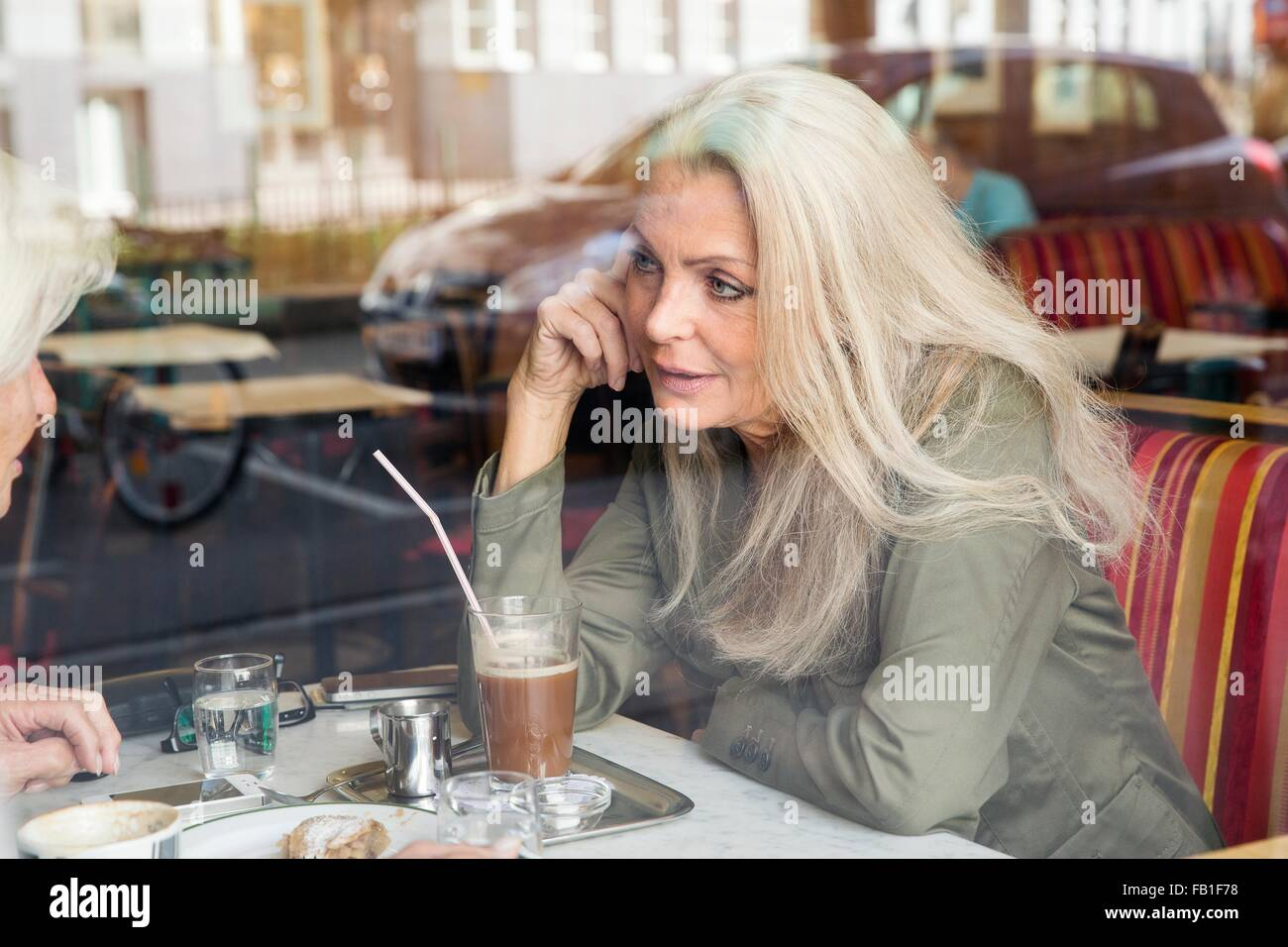 Mother and daughter sitting together in cafe, seen through cafe window - Stock Image
