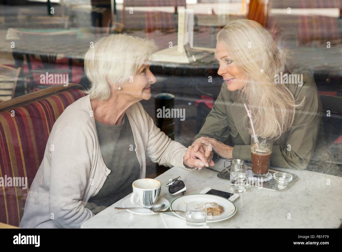 Mother and daughter sitting together in cafe, holding hands, seen through cafe window - Stock Image
