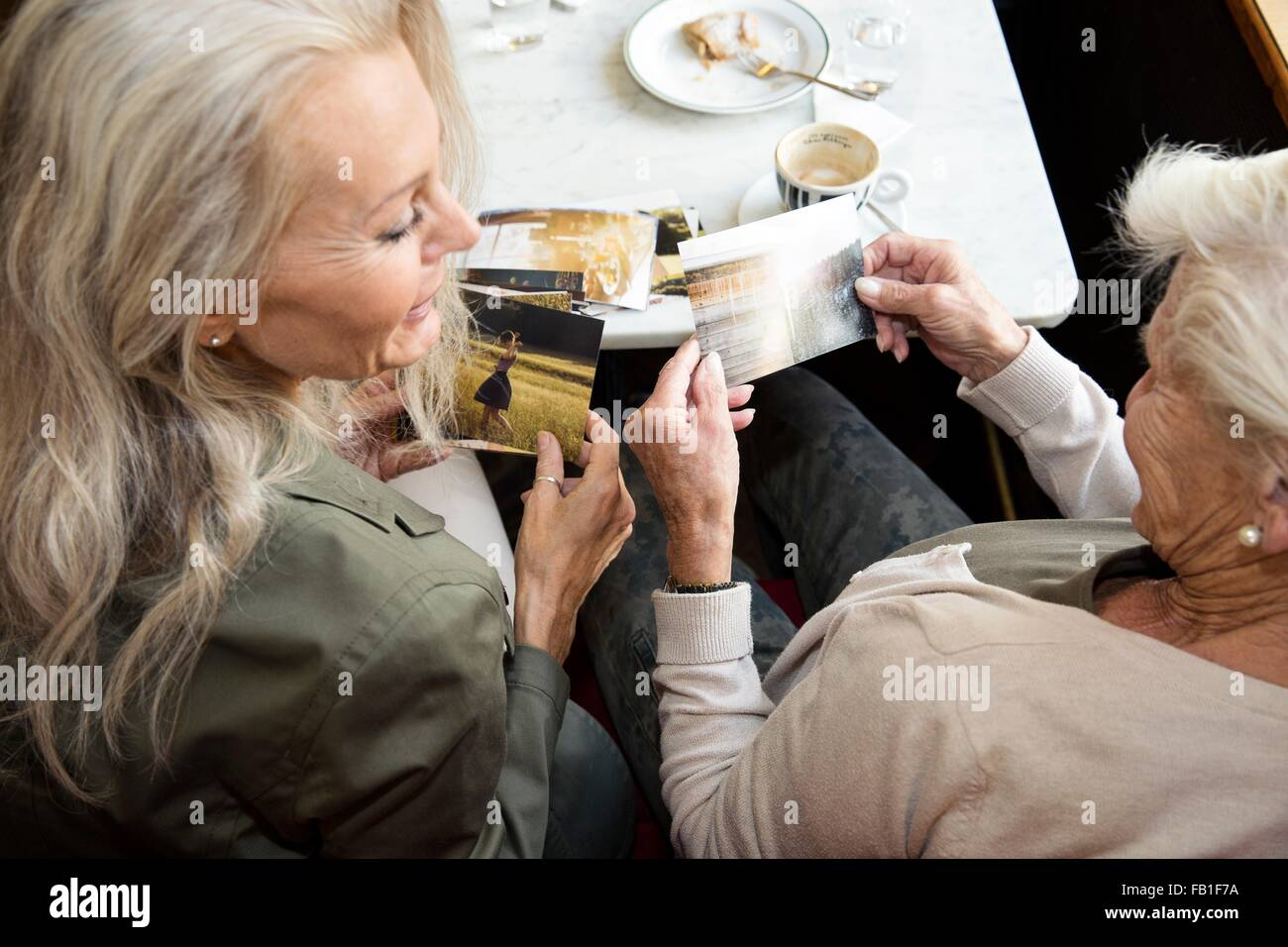 Mother and daughter sitting together in cafe, looking at photographs, rear view - Stock Image