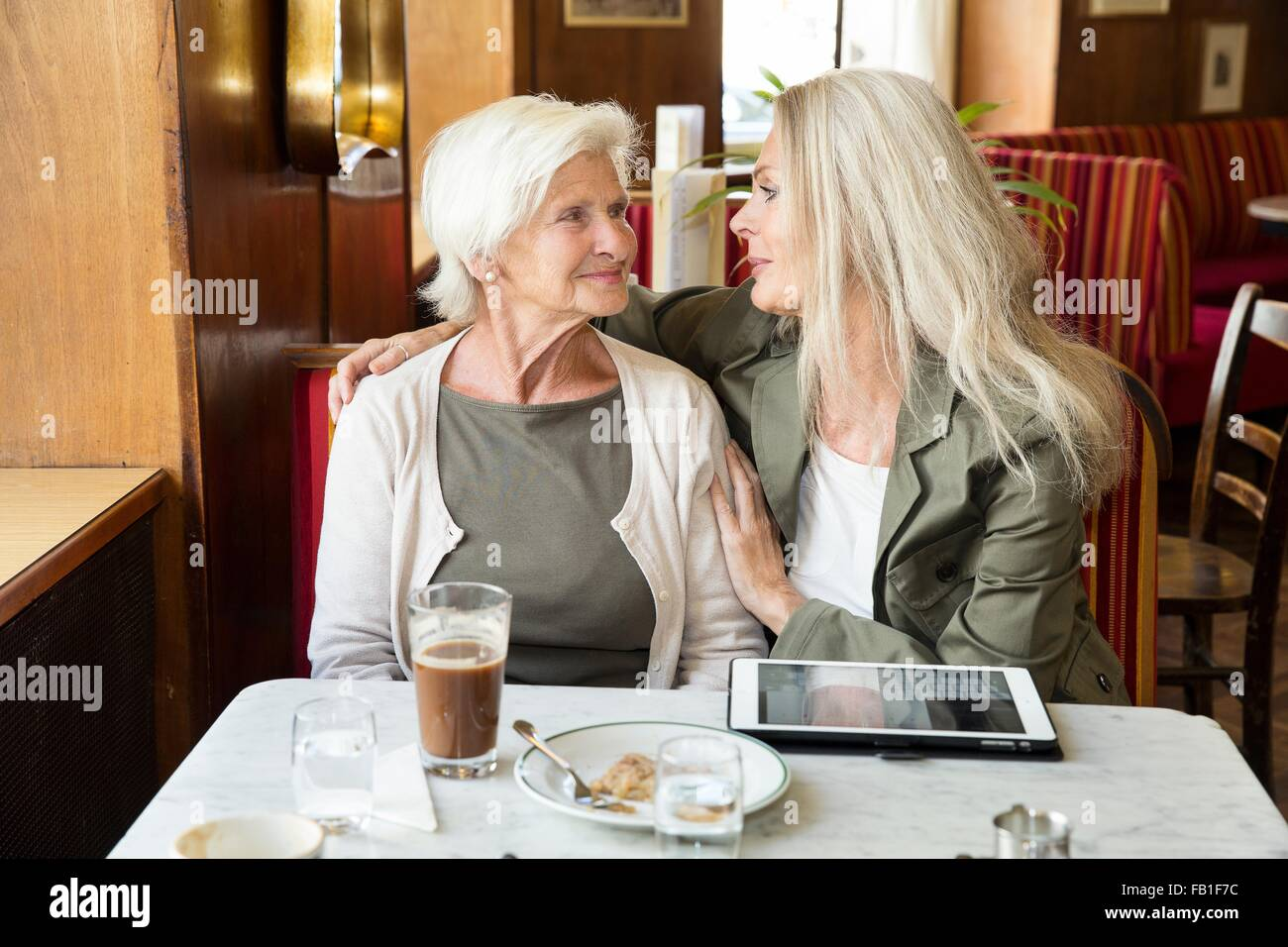 Mother and daughter sitting together in cafe, daughter's arm around mother, digital tablet on table - Stock Image
