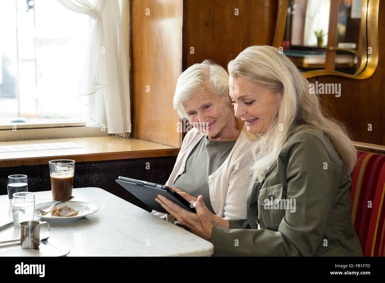 Mother and daughter sitting together in cafe, looking at digital tablet - Stock Image
