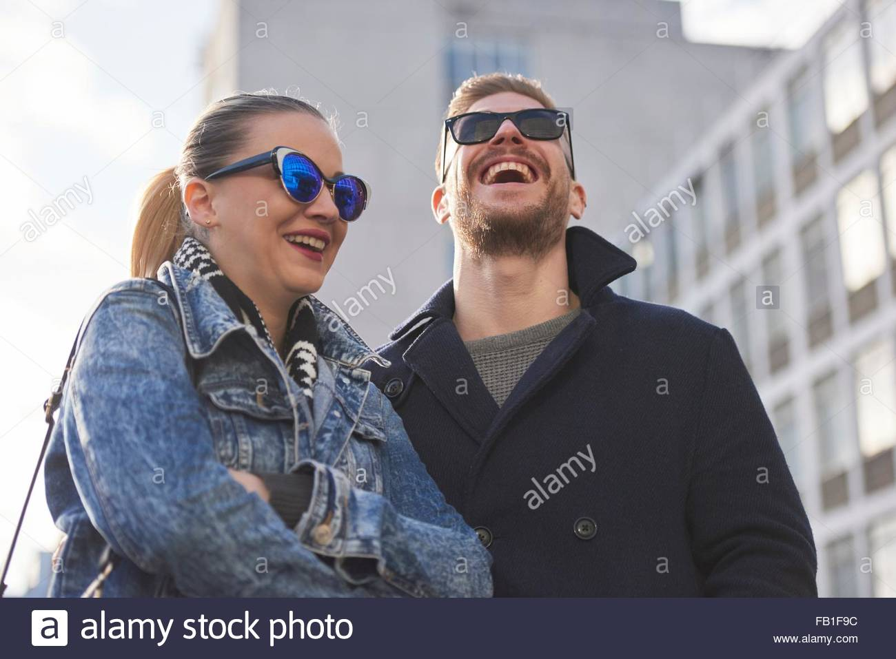 Young couple wearing sunglasses and warm clothing, outdoors - Stock Image