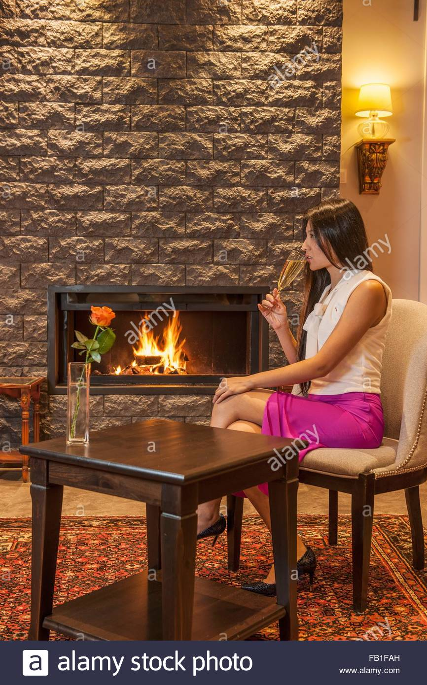 Business woman drinking champagne, sitting next to fireplace in hotel lobby - Stock Image