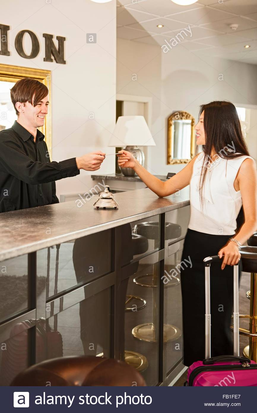 Business woman checking into hotel - Stock Image