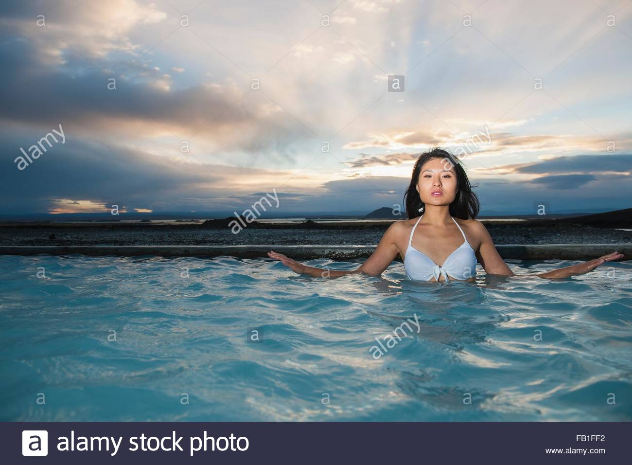 Woman enjoying the warm water, in geothermal bath, North Iceland - Stock Image