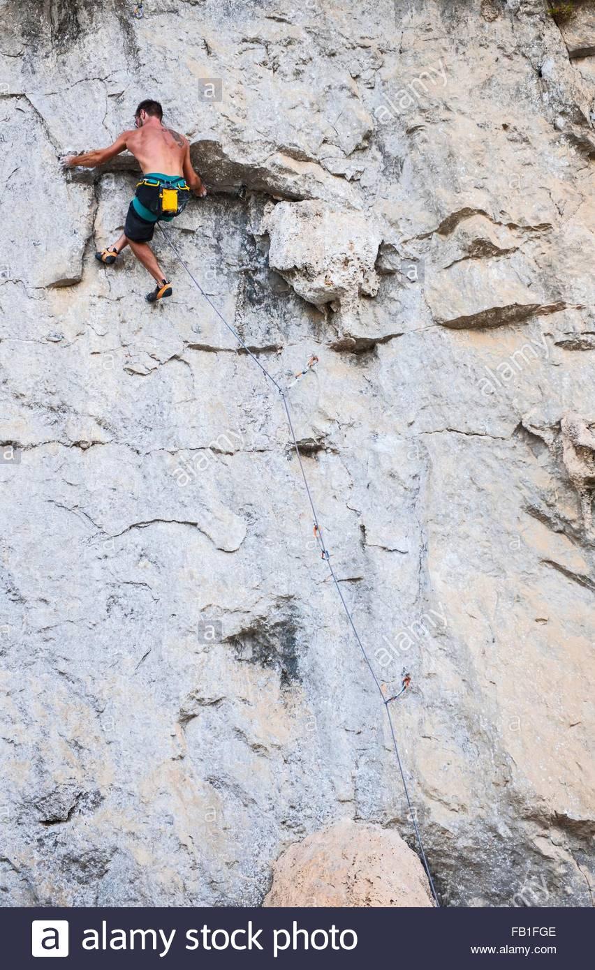 Low angle rear view of rock climber, climbing rock face of Riverside Crag, Yangshuo, Guangxi Zhuang, China - Stock Image
