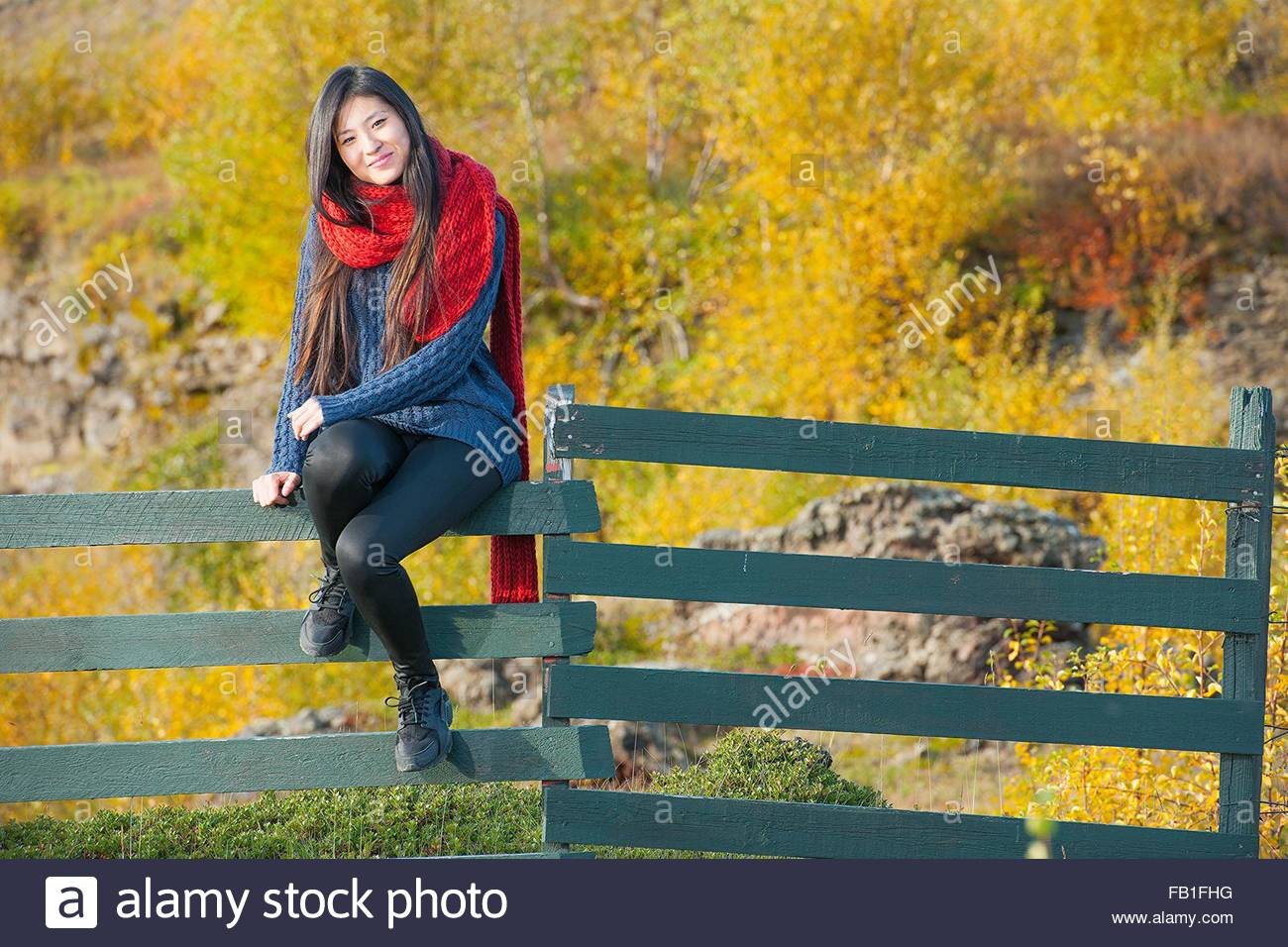 Mid adult woman wearing red wool scarf sitting on fence looking at camera smiling - Stock Image