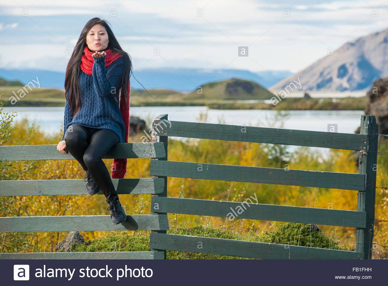 Mid adult woman wearing red wool scarf sitting on fence looking at camera blowing kiss, Myvatn, North Iceland, Iceland - Stock Image