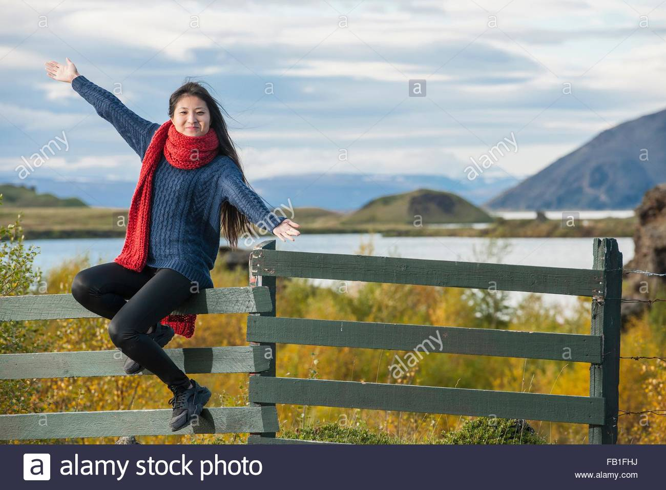 Mid adult woman wearing red wool scarf sitting on fence arms open looking at camera smiling, Myvatn, North Iceland, - Stock Image