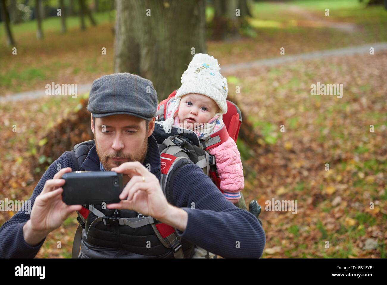 Mid adult man in park wearing flat cap carrying daughter on back in baby carrier taking selfie using smartphone - Stock Image