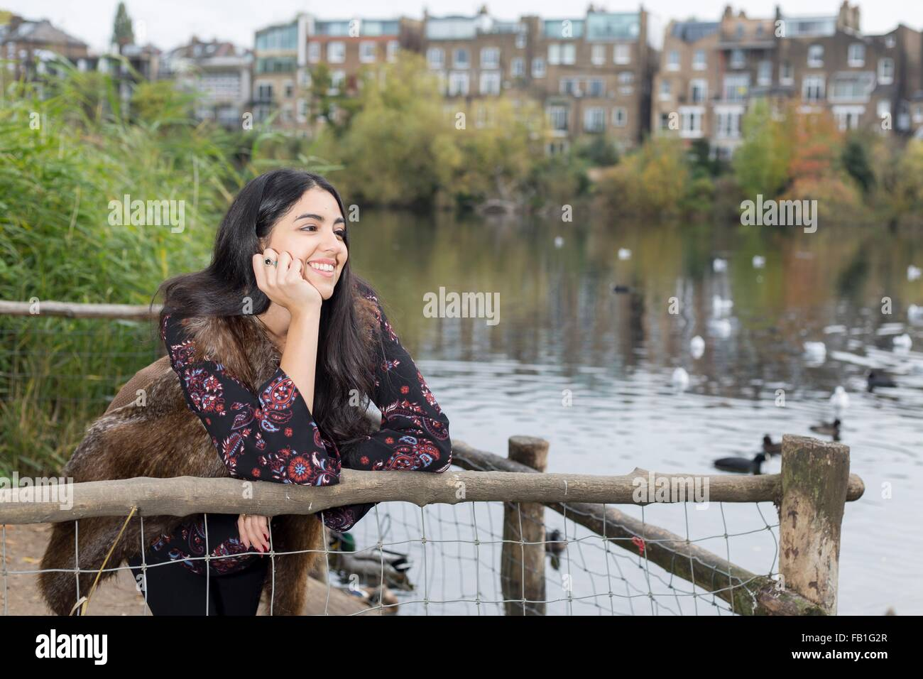 Young woman relaxing by lake, Hampstead Heath, London - Stock Image