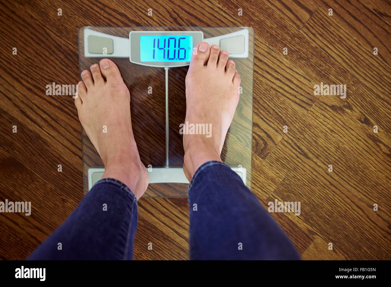 Woman standing scales with digital display, low section, elevated view - Stock Image