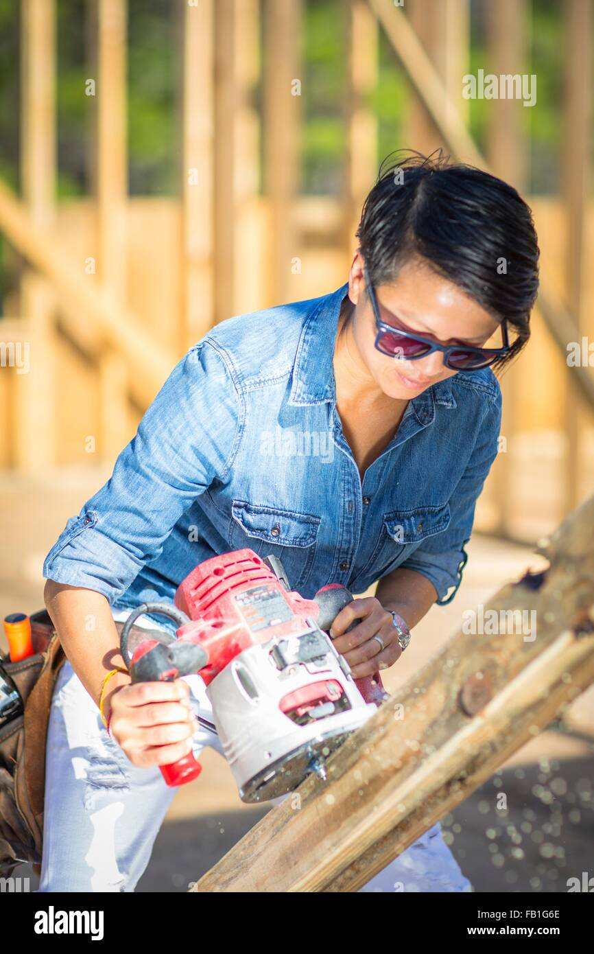 Mid adult woman using power tool, building her own home - Stock Image