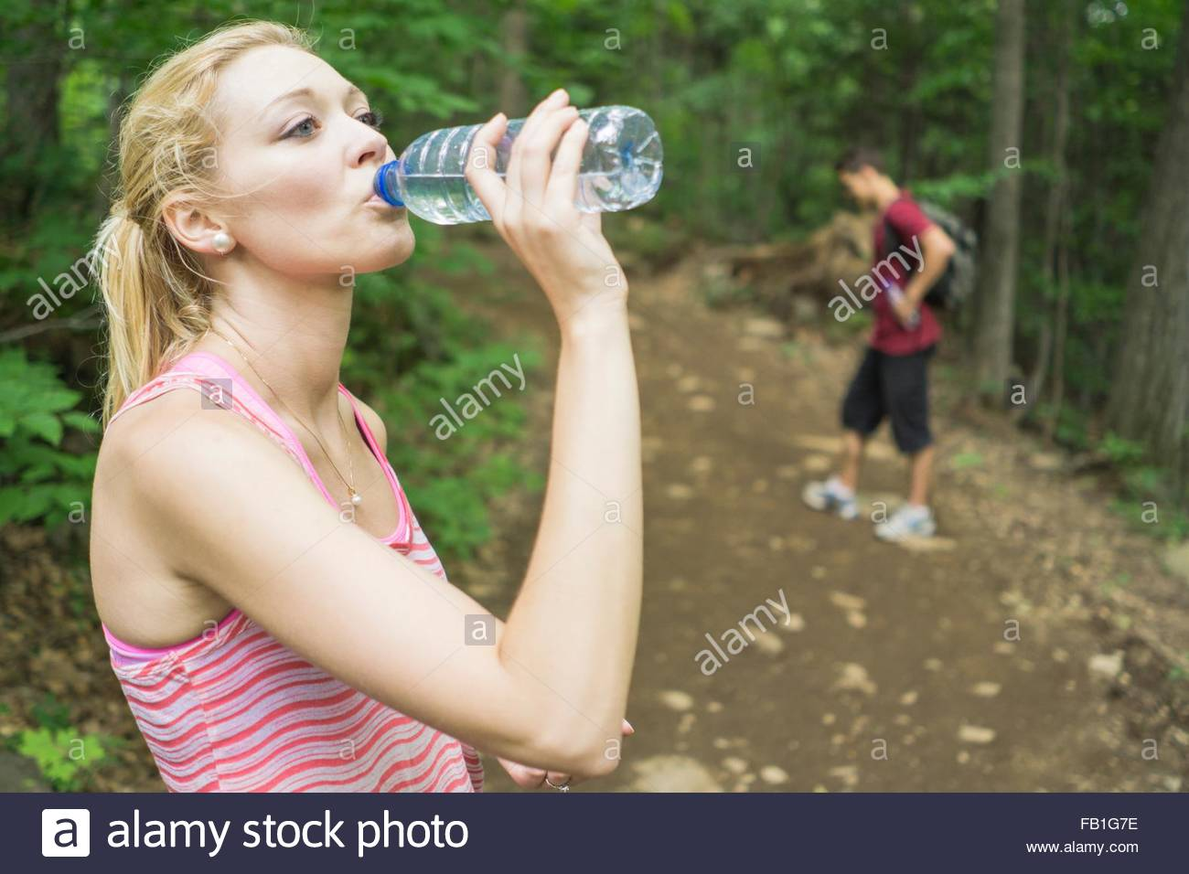 Young woman in forest, drinking from water bottle - Stock Image