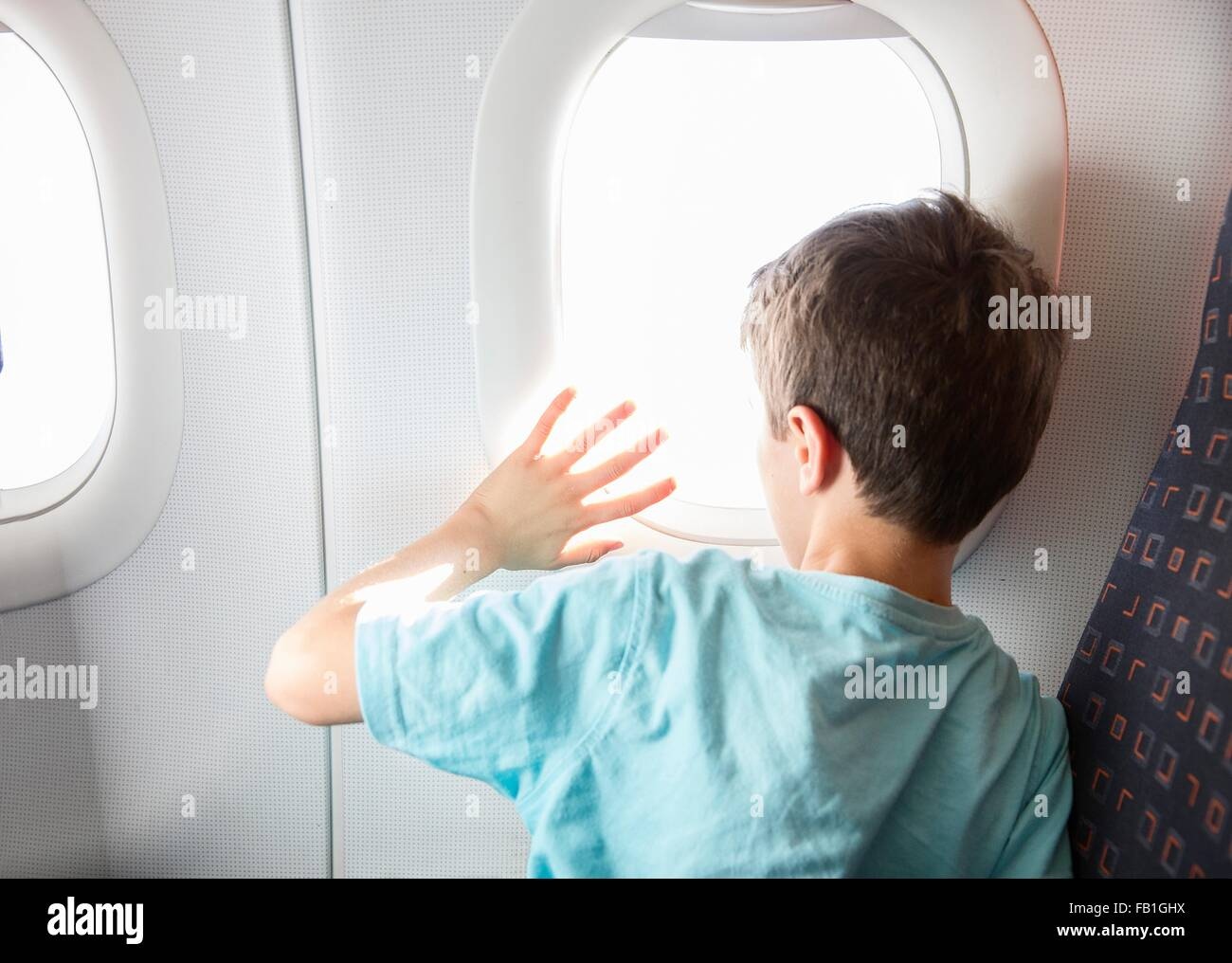 Rear view of boy looking and waving through airplane window - Stock Image