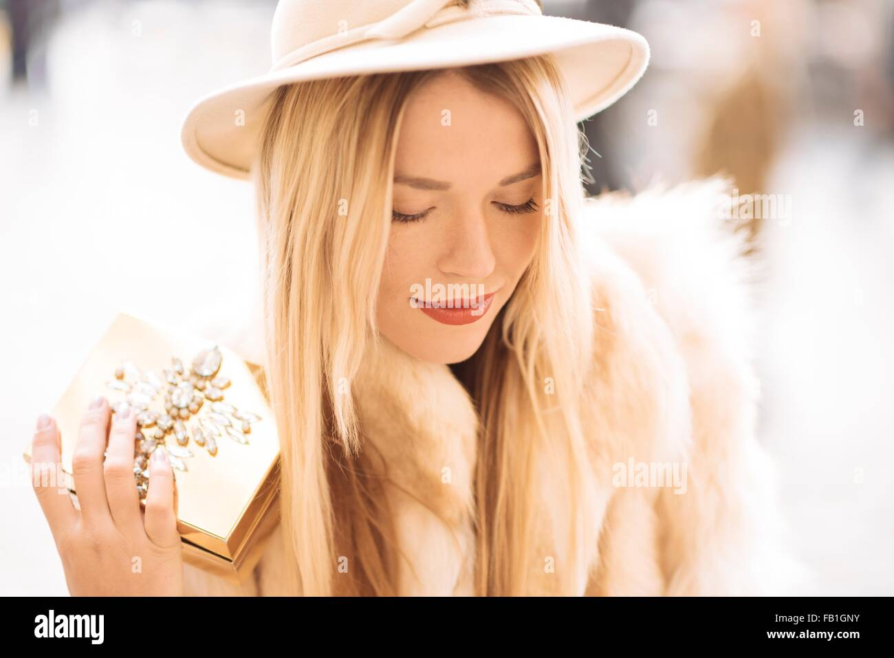 Stylish young woman holding gold jewelry box, Covent Garden, London, UK - Stock Image