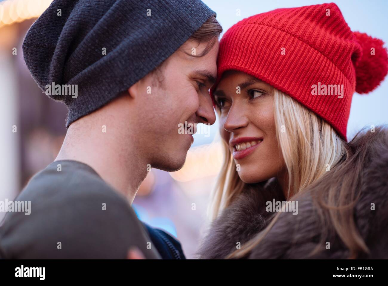 Head and shoulder shot of romantic young couple wearing knit hats - Stock Image