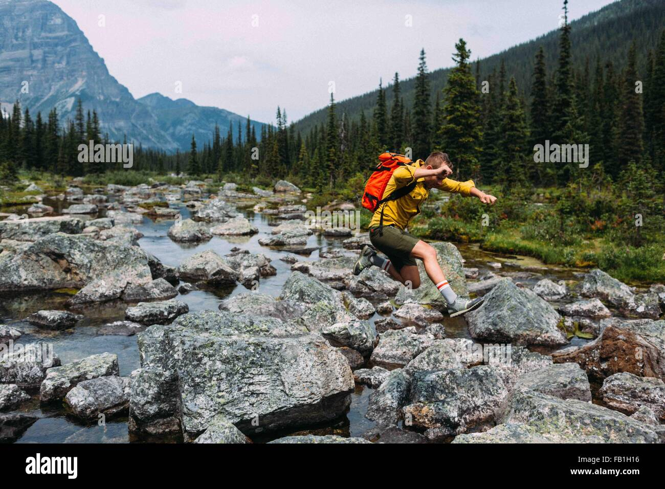 Side view of mid adult man carrying backpack jumping over rocky riverbed, Moraine lake, Banff National Park, Alberta - Stock Image