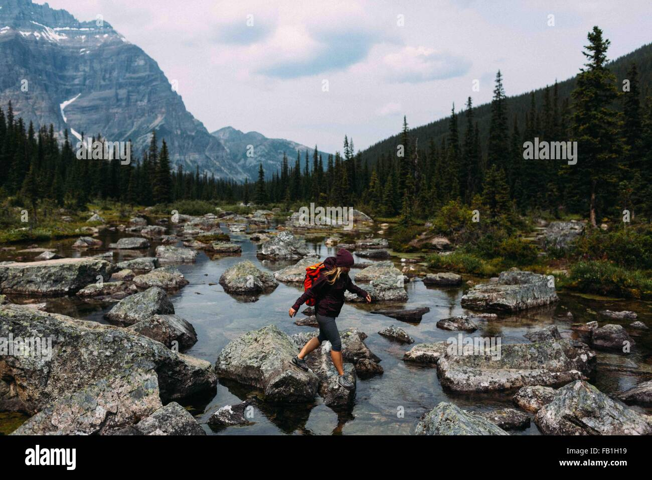Side view of mid adult woman walking on rocky riverbed, Moraine lake, Banff National Park, Alberta Canada - Stock Image