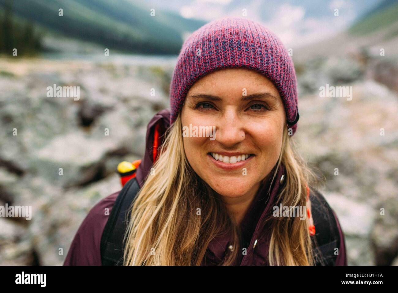 Portrait of mid adult woman wearing knit hat looking at camera smiling, Moraine lake, Banff National Park, Alberta - Stock Image