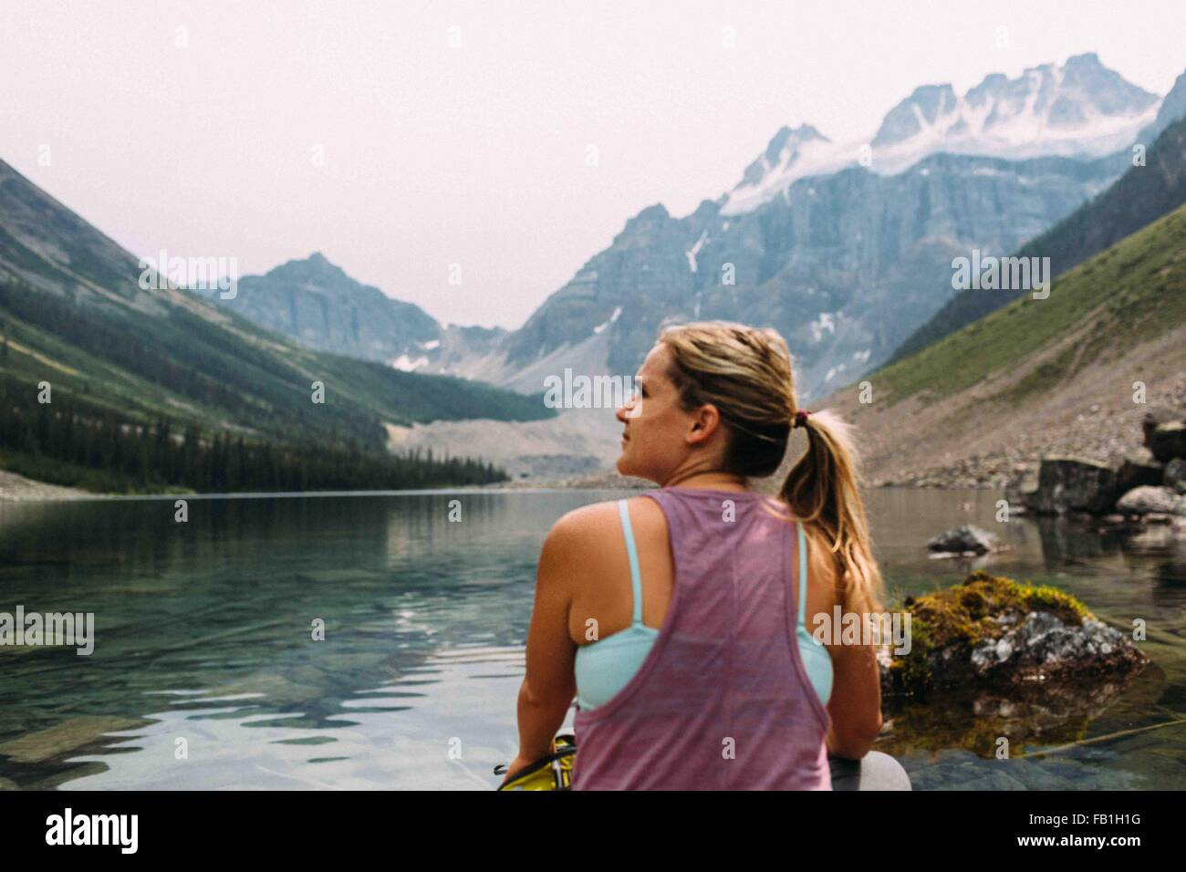 Rear view of mid adult woman sitting at waters edge looking away, Moraine Lake, Banff National Park, Alberta Canada - Stock Image
