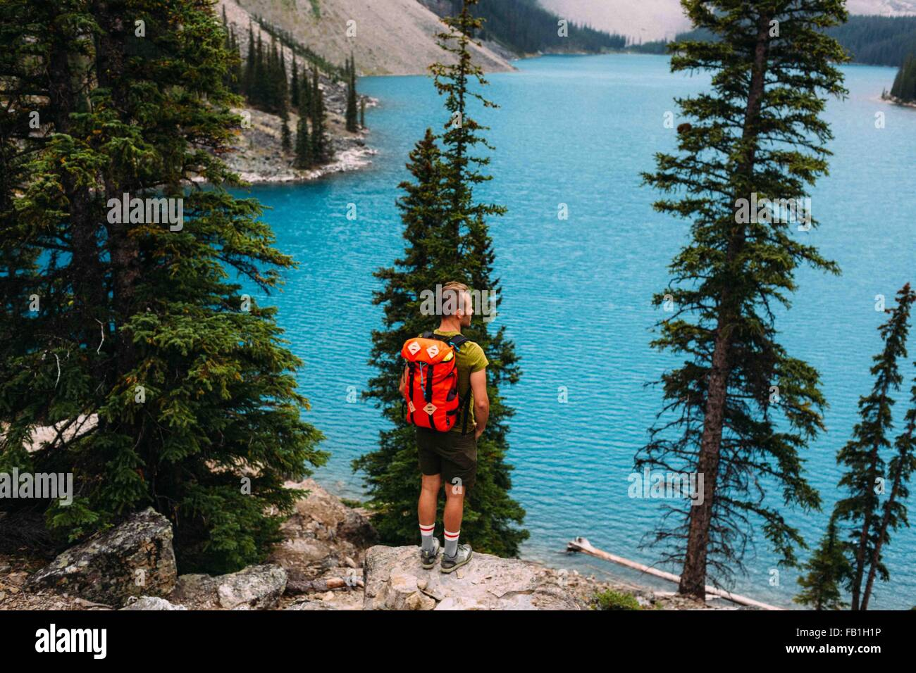 Rear view of mid adult man standing on cliff edge looking at elevated view of Moraine lake, Banff National Park, - Stock Image