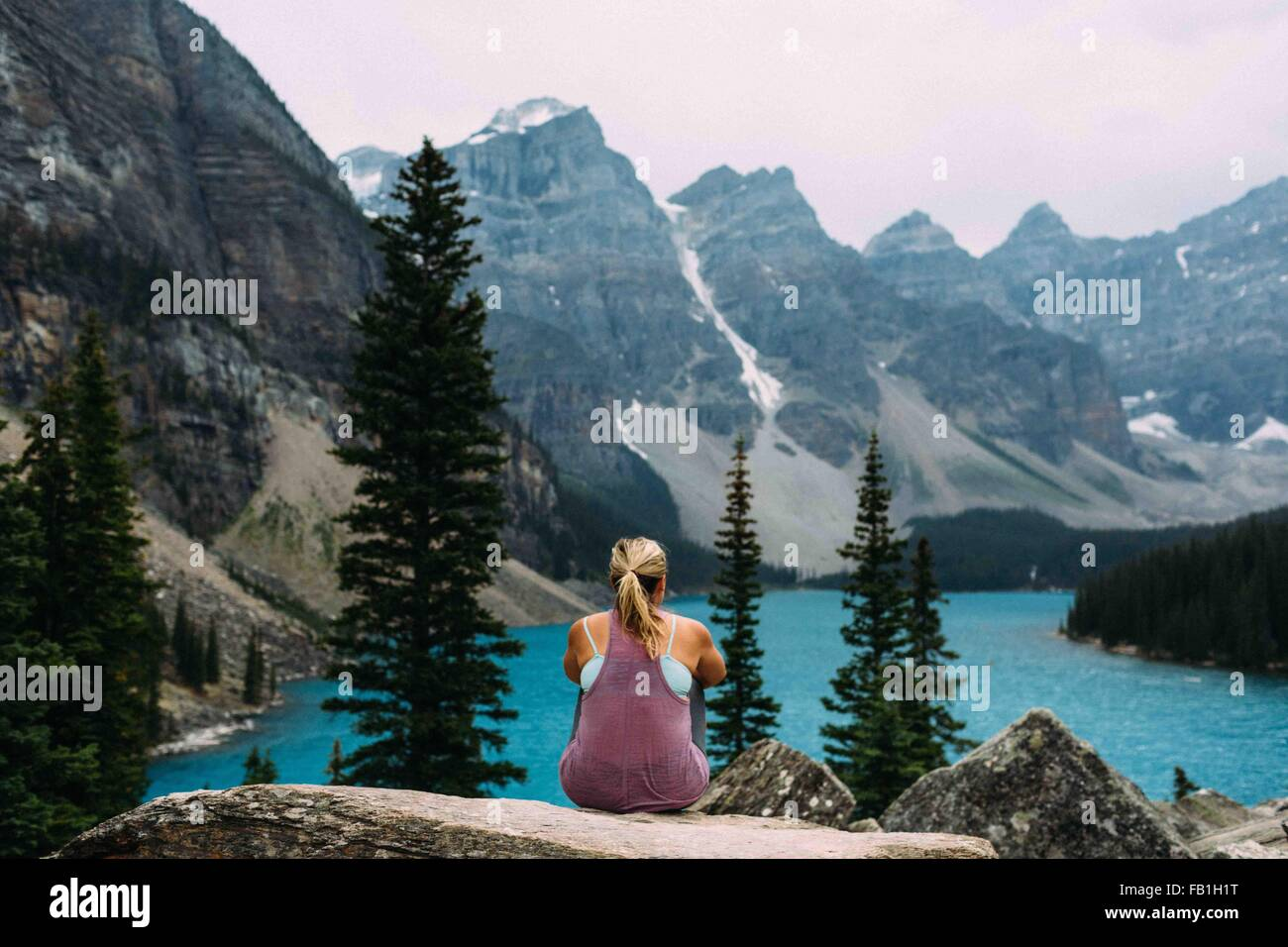 Rear view of mid adult woman on cliff edge looking at elevated view of Moraine lake, Banff National Park, Alberta - Stock Image