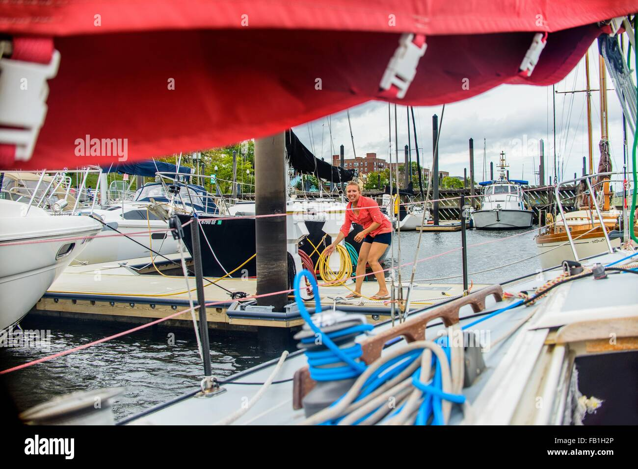 Young woman on marina pier mooring sailboat looking at camera smiling - Stock Image