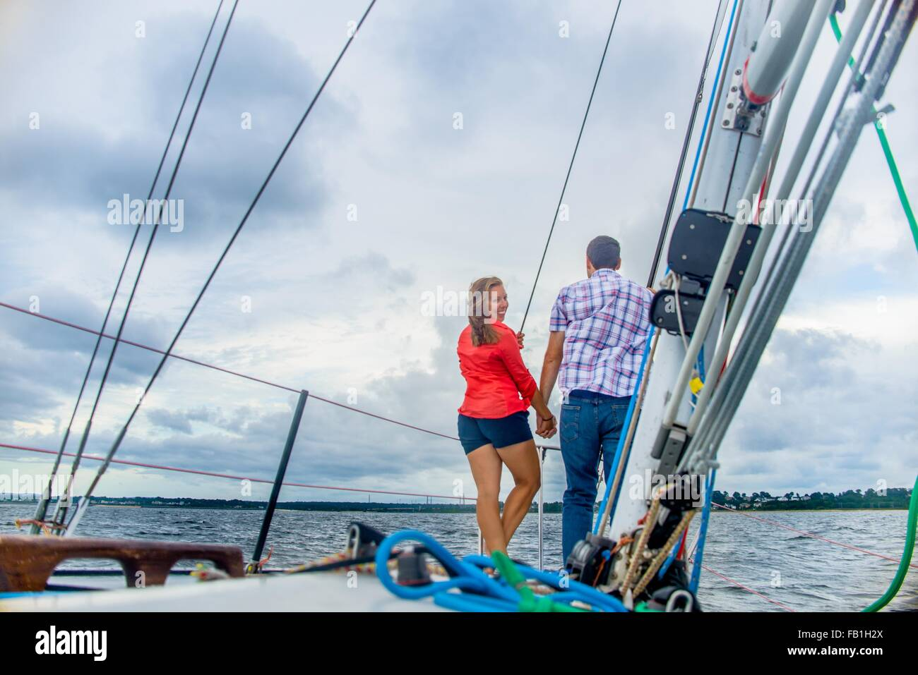 Rear view of couple on bow of boat holding hands, looking over shoulder at camera smiling - Stock Image