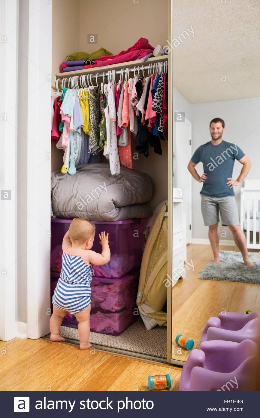 Mid adult man watching baby daughter search box in wardrobe - Stock Image
