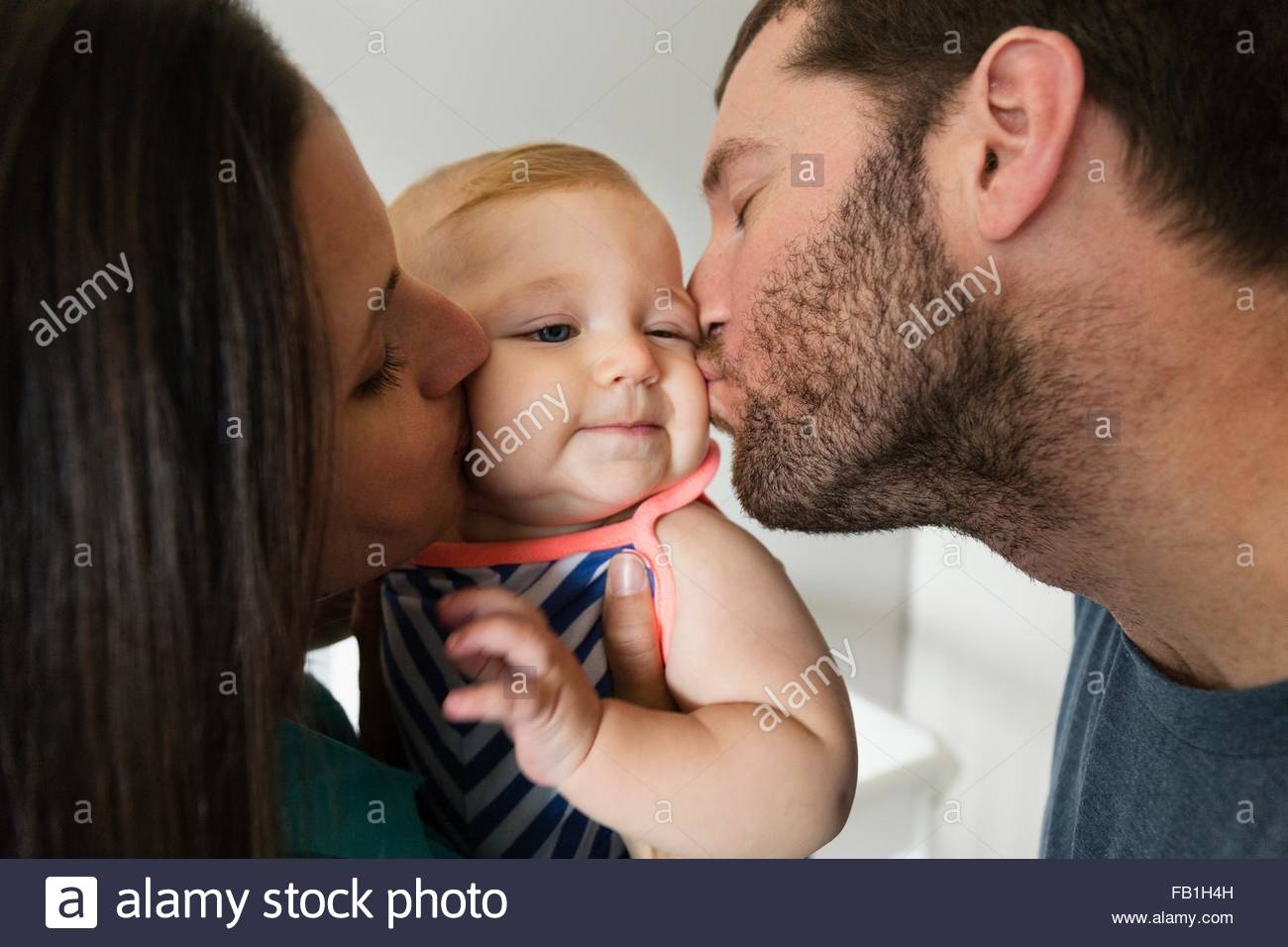 Close up of mid adult couple kissing baby daughter on each cheek - Stock Image
