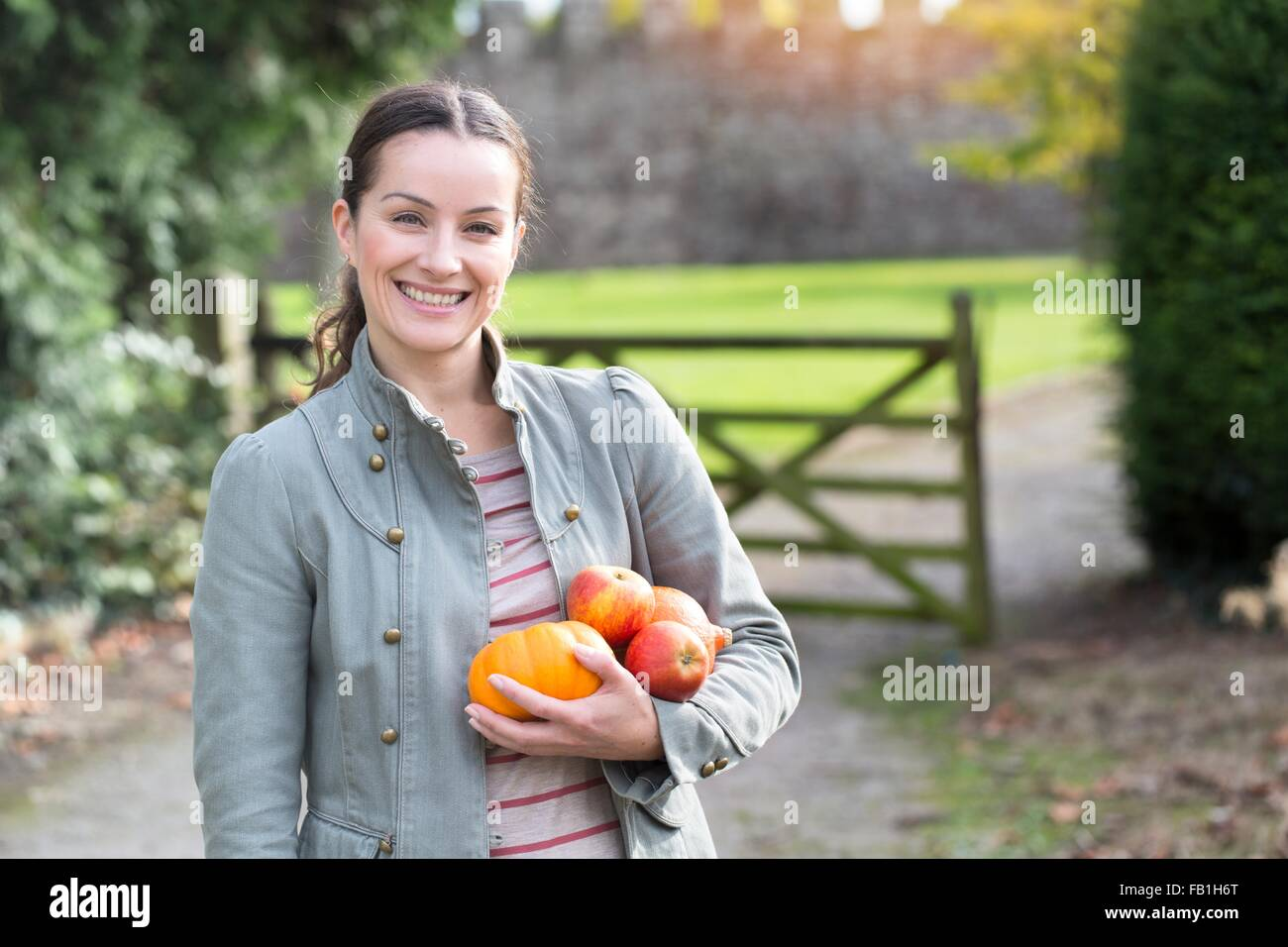 Portrait of woman holding apples and pumpkin at Thornbury Castle, South Gloucestershire, UK - Stock Image