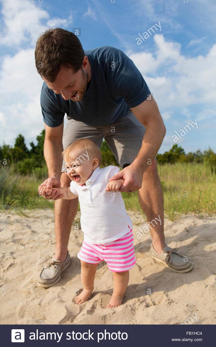 Mid adult man holding baby daughters hands while toddling in sand - Stock Image