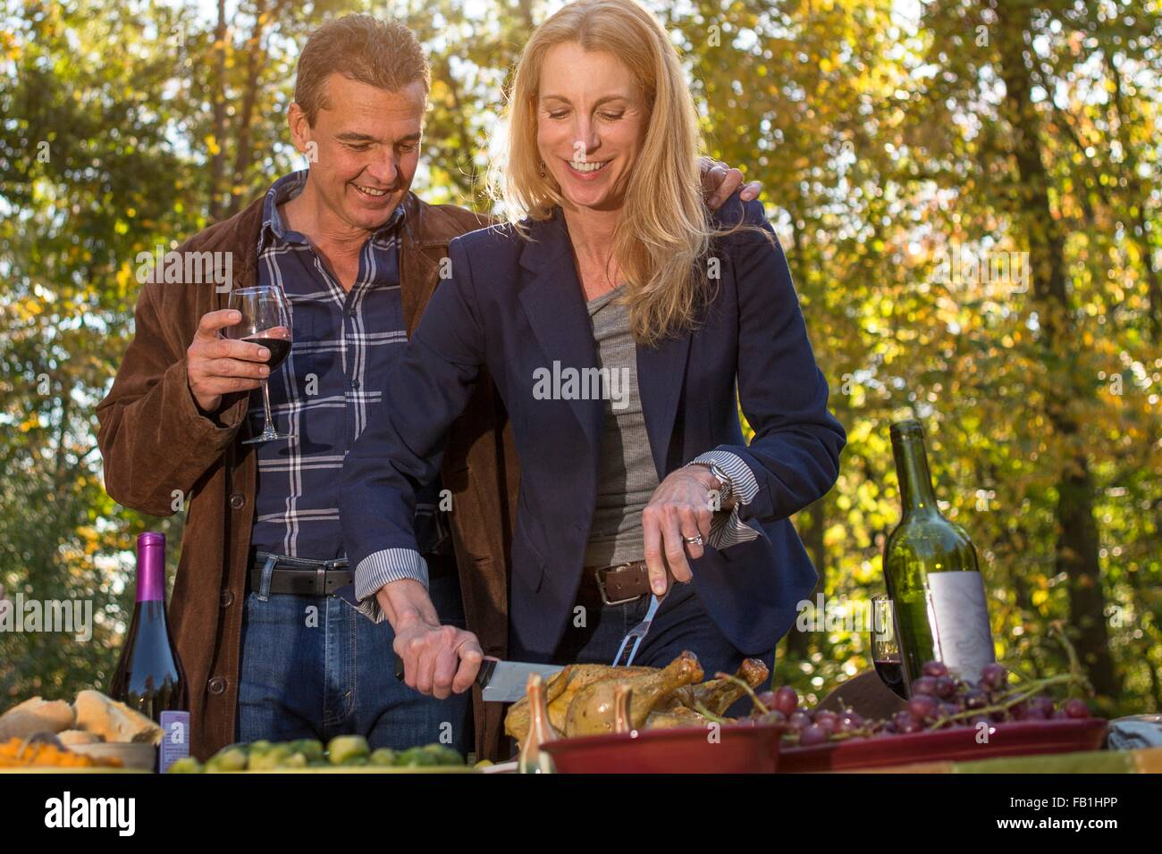 Mature couple carving roast chicken at garden dinner party - Stock Image