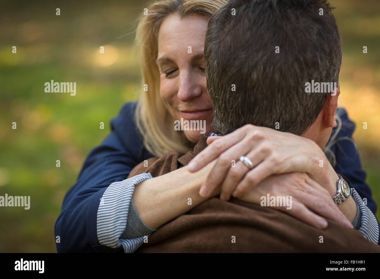 Close up of romantic mature couple hugging in garden - Stock Image