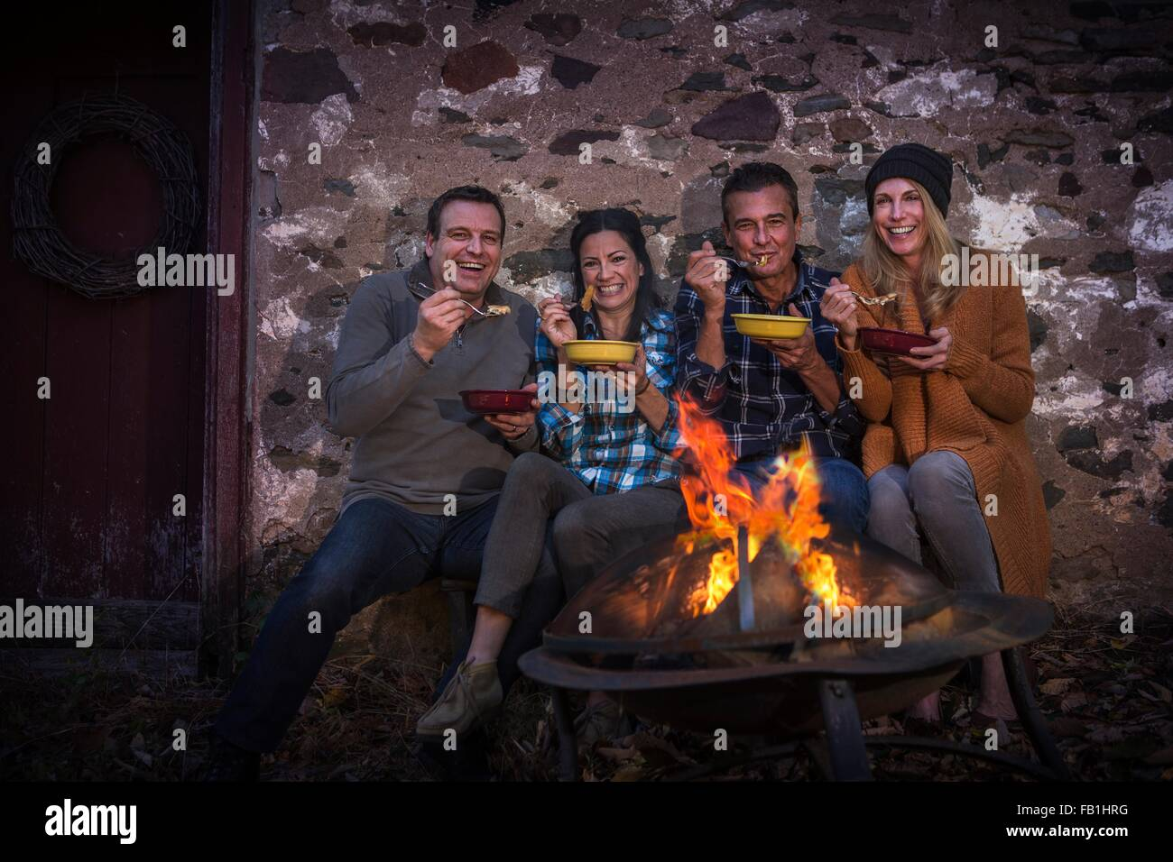 Portrait of two mature couples eating in front of campfire at night - Stock Image