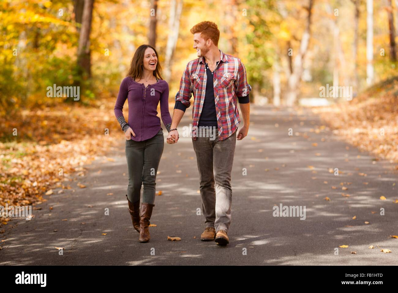 Romantic young couple strolling in autumn forest Stock Photo