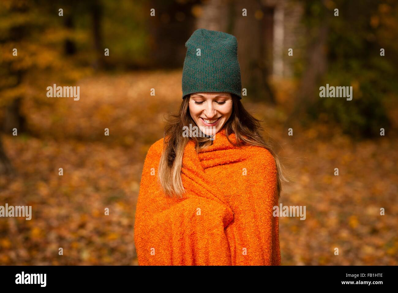 Young woman wrapped in orange blanket in autumn forest - Stock Image
