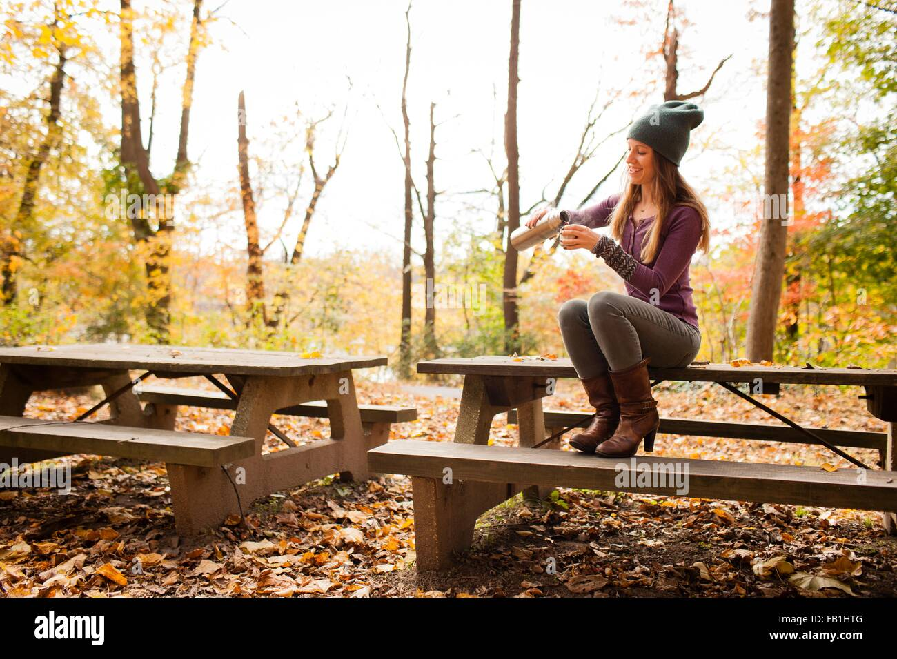 Young woman pouring drink on picnic bench in autumn forest - Stock Image