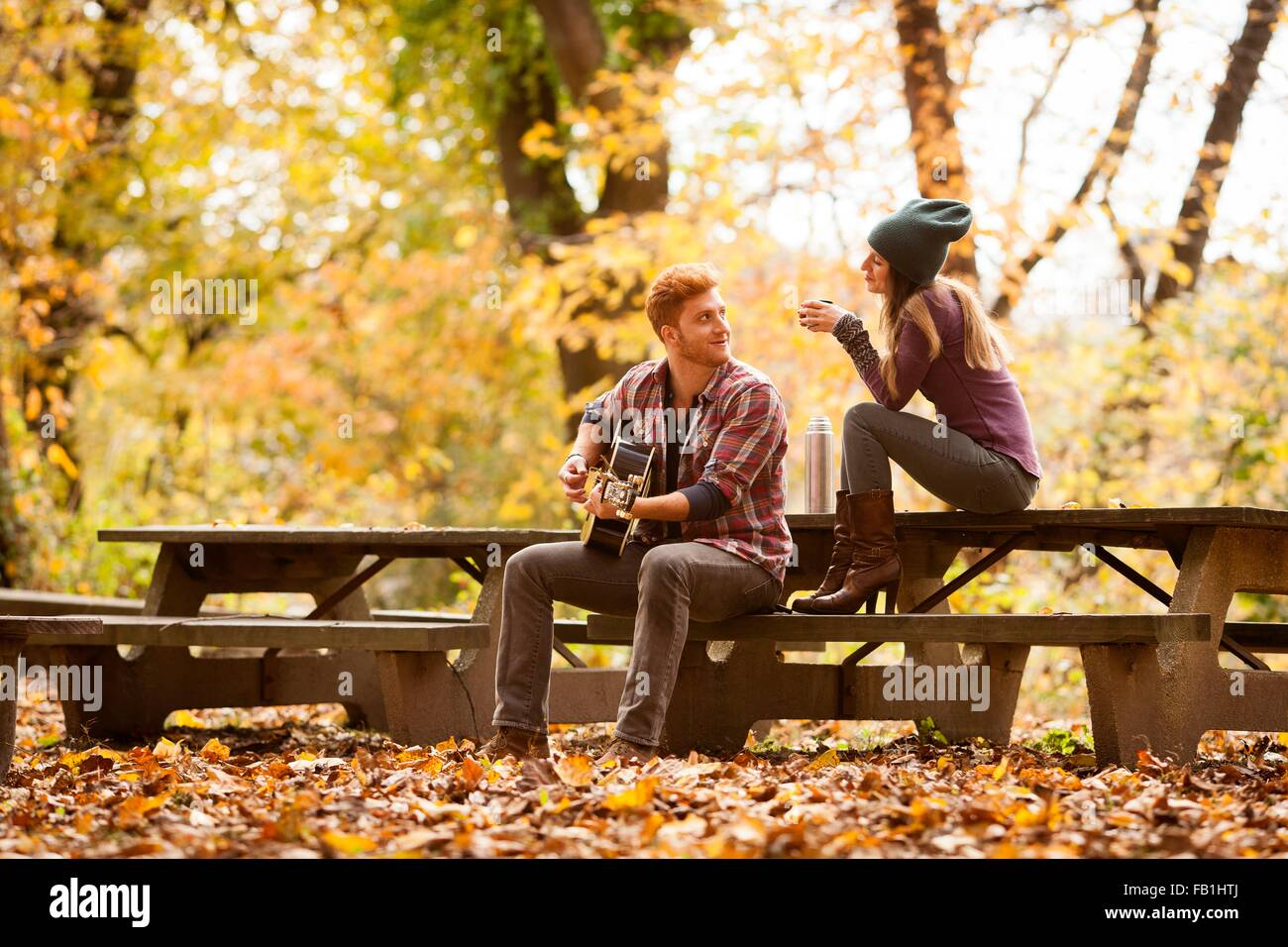 Young couple playing guitar on picnic benches in autumn forest - Stock Image
