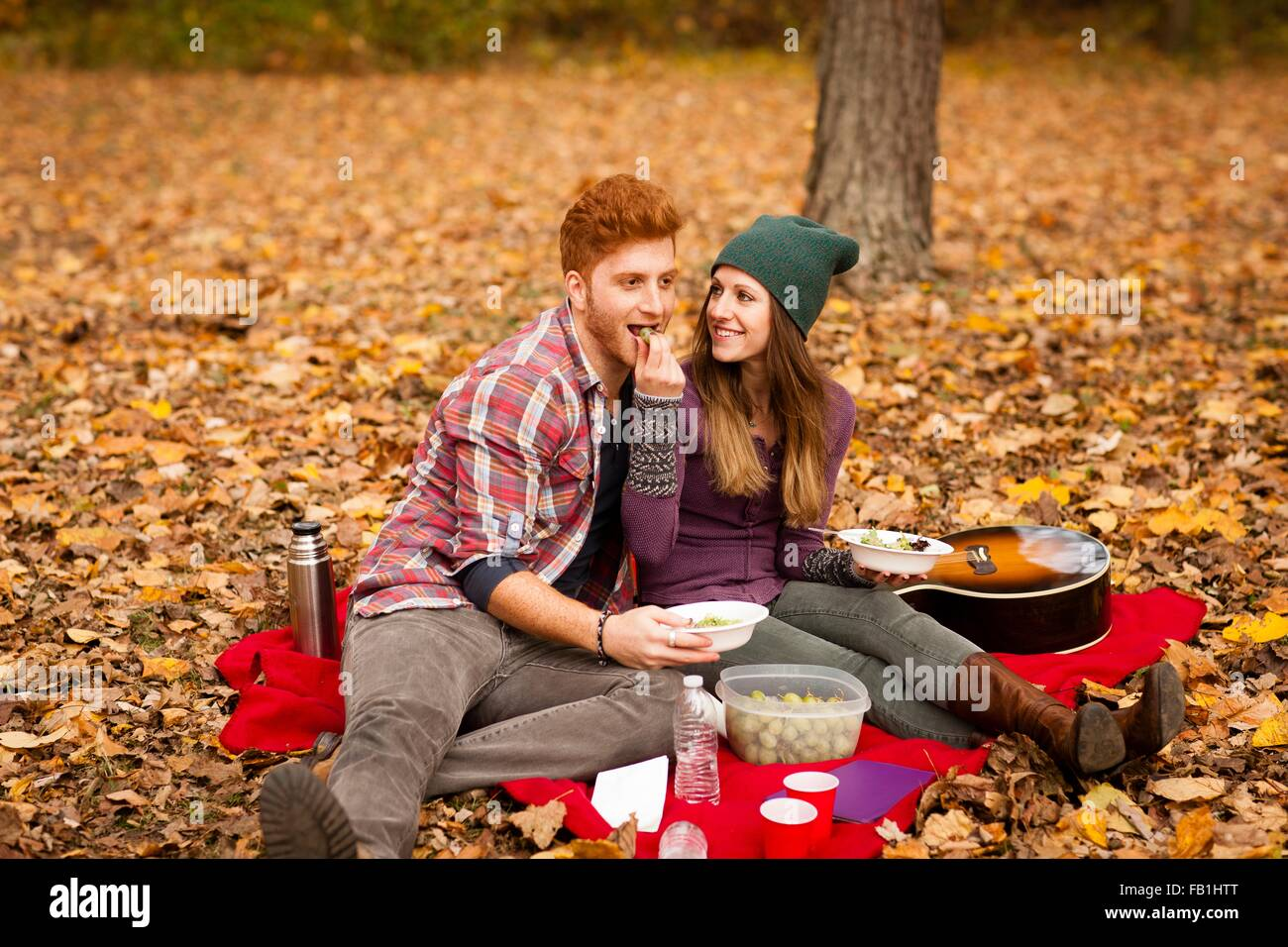 Young couple having picnic in autumn forest Stock Photo