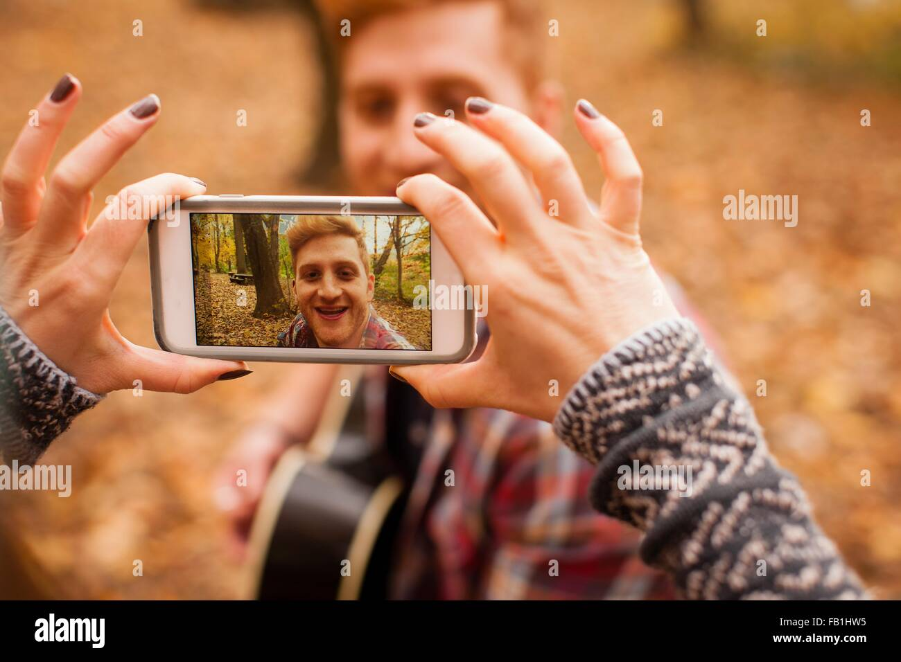 Hands of young woman photographing boyfriend on smartphone in autumn forest - Stock Image