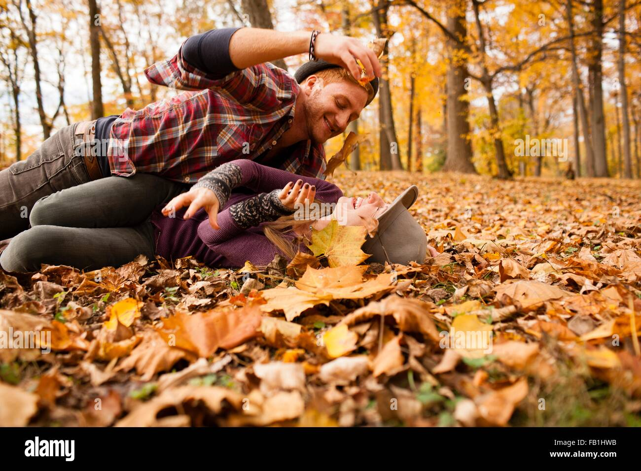 Young couple play fighting with autumn leaves in forest - Stock Image